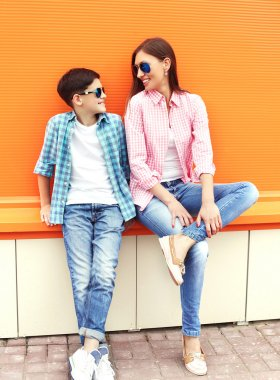Happy mother and son teenager wearing a checkered shirt and sung