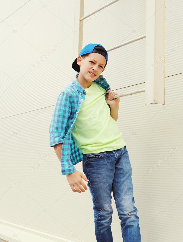 Стильный ребенок мальчик, одетый в рубашку и бейсболку в городе — стоковое  фото 3ab3f82c116