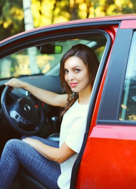 Beautiful young woman driver behind the wheel red car