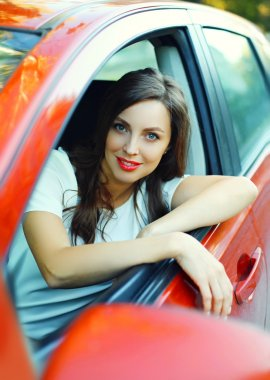 Portrait beautiful woman driver behind the wheel red car