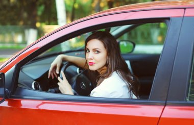 Young beautiful woman driver behind the wheel red car