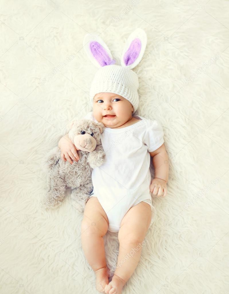 Feliz dulce bebé en de punto sombrero con un conejo orejas y teddy ...