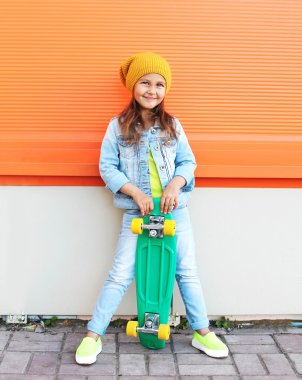 Stylish little girl child with skateboard having fun in city stock vector