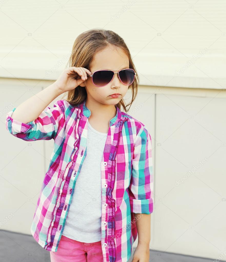 38b43c642afeb Mode pour enfant petite fille portait une chemise à carreaux rose et des  lunettes de soleil en ville — Image de Rohappy