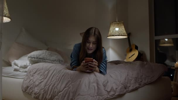 Woman using phone in bed at night. Mobile girl typing smartphone