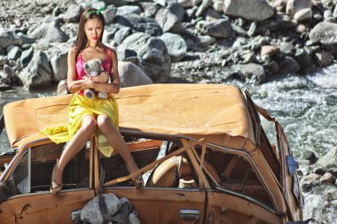 Woman in baby doll stile sitting on a broken car in the sun with teddy bear in hand