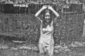 Dívka v plíživý šaty s dlouhými vlasy v kapičky vody v městské kašny