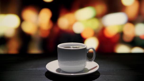 Šálek kávy na dřevěném stole v kavárně před oknem s výhledem na noční město