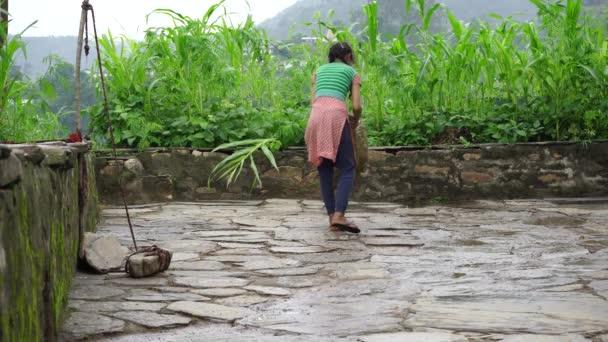 Junges indisches Mädchen putzt frühmorgens mit einem Besen den Hof