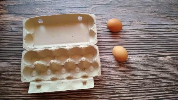 egy női kéz kivesz egy bézs tojást egy tojásos dobozból.