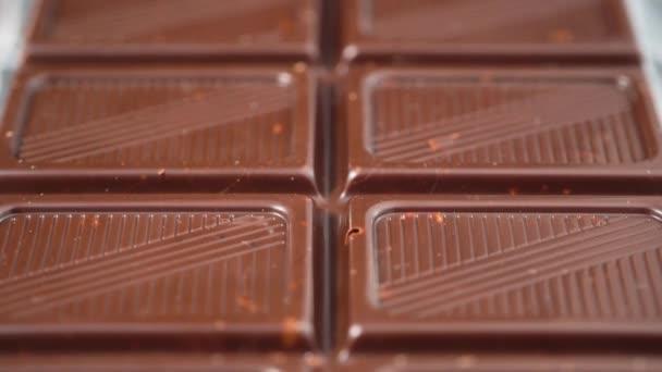 Čokoládová tyčinka. Kamera se pohybuje dopředu nad plátky čokolády
