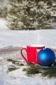 červený hrnek s vánoční koule v zimním lese