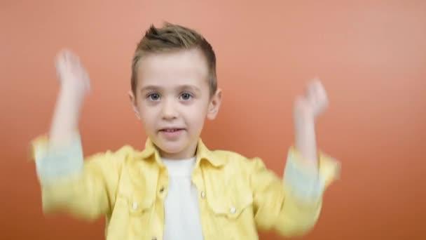 Wenig Spaß glücklicher Junge 4-5 Jahre alt in gelbem Hemd posiert geballte Fäuste und macht Siegergeste sagen Ja isoliert auf orangefarbenem Hintergrund Studio. Lebensstil-Konzept der Menschen