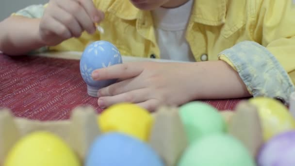 Creative Caucasian little boy painting Easter eggs. Preschooler kid drawing an Easter pattern on a blue egg. Preparation for the holiday Easter. Close up view