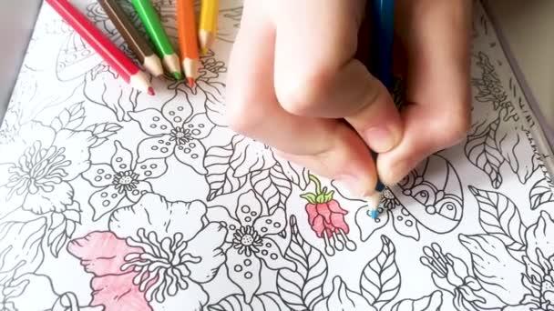 Moszkva, Oroszország, Október 2020: Valaki fiatal kéz festési minták anti-stressz színező könyv kék ceruza, és színes ceruzák mellettük. Zen művészet, firka minták fekete-fehér. Zen kusza, kifestőkönyvek