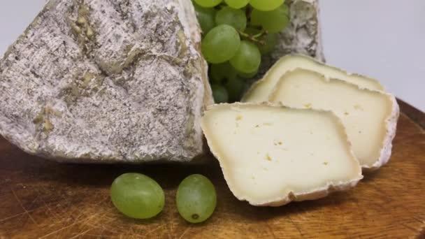 Talíř z různých plesnivých kozích sýrů na dřevěné desce se zelenými hrozny
