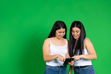 The brunette sisters are looking at the photos on the digital tablet and smiling sweetly. Green background and empty space. High quality photo