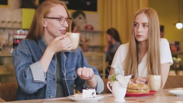 İki çekici genç kadın bir kafede kahvaltı yapıyor. İki arkadaş kahve içiyor.