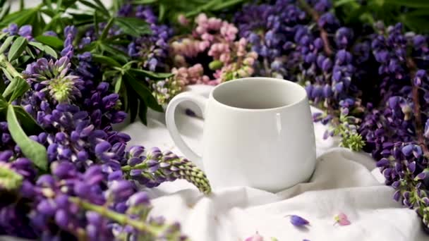 spring composition with flowers and a cup of tea on a white sheet. flowers and a cup of coffee among the flowers. Flat lay, top view