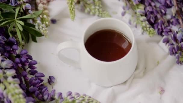 jarní složení s květinami a šálkem čaje na bílém prostěradle. květiny a šálek kávy mezi květinami. Byt ležel, horní pohled