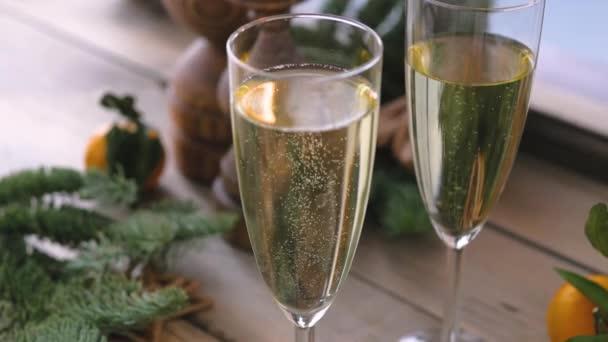 Vánoční stolek u zimního okna. Dvě sklenice šampaňského, svíčky v dřevěných svícnech a mandarinky obklopené čerstvými smrkovými větvemi.