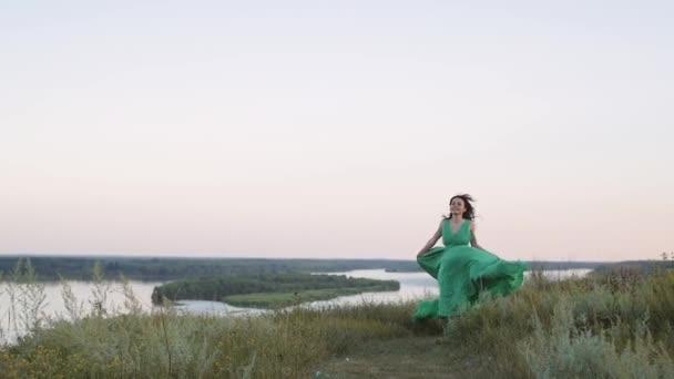 fiatal nő zöld ruhában pózol egy gyönyörű táj hátterében. vonzó nő kalap és hosszú ruha