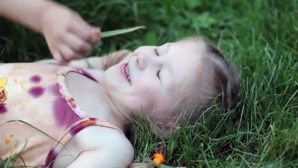 Dívka ležela v trávě a směje se
