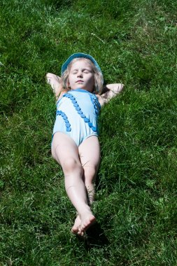 Happy child sleeping on green grass