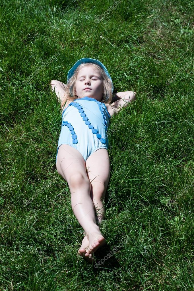Happy child sleeping on green grass