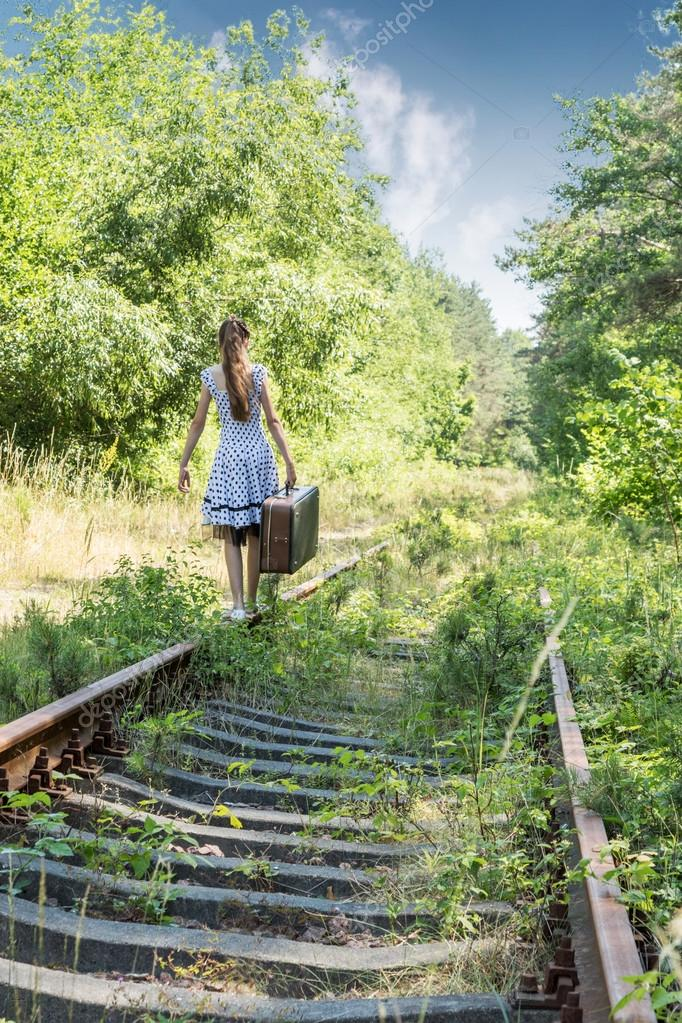 Girl with a suitcase walking on rails
