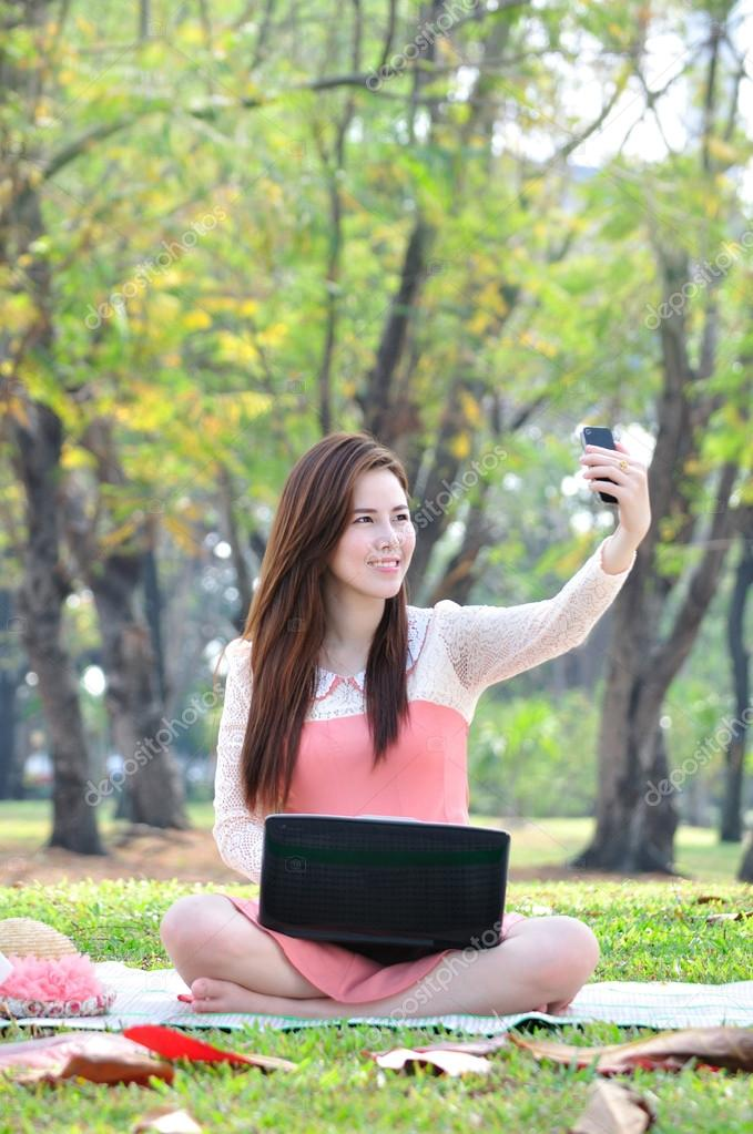 woman sitting on wooden mat and take a photo.