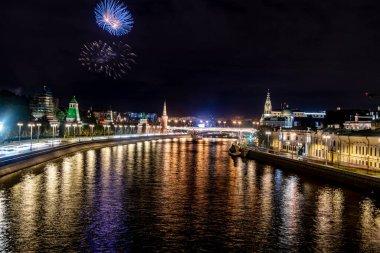 Nehre yansıyan gece nehir ışıklarıyla manzara ve kıyıda kuleleri olan antik Kremlin.