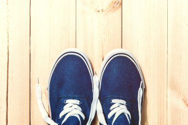 Blue sneakers on wooden background with copy space. Top view.