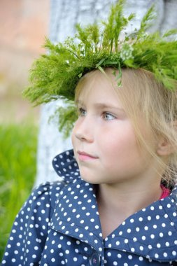Toddler girl with grass head wreath on