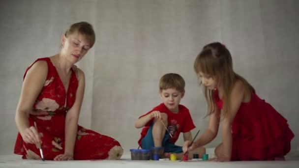 Mujer con los niños dibujar en papel — Vídeo de stock ...