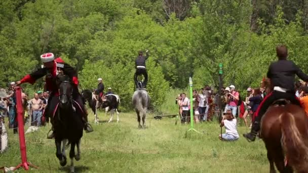 Riders riding on horses, they saber cuts water bottles
