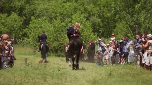 Reiter reiten auf Pferden, sie zeigen Akrobatik
