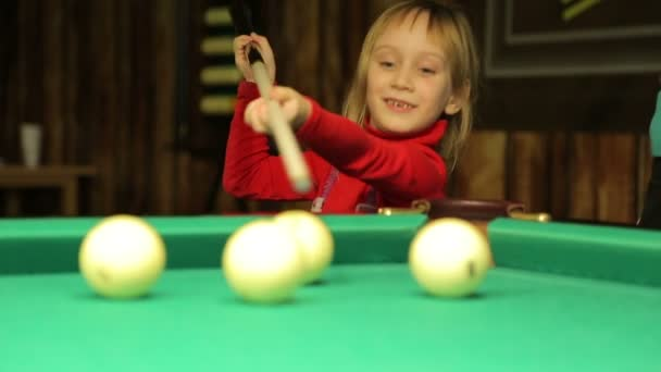 Girl plays billiards