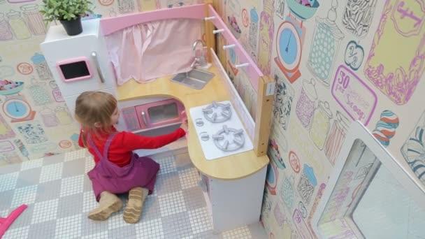 Dívka si hraje s hračkou kuchyní, pohled shora