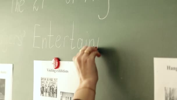 Učitel zapisuje na tabuli ve škole