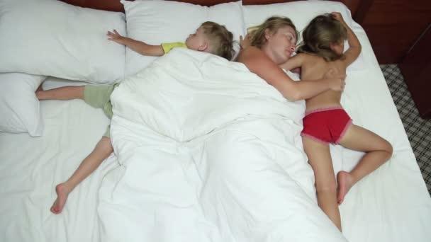 Nő fekszik az ágyban alvó gyermekeivel