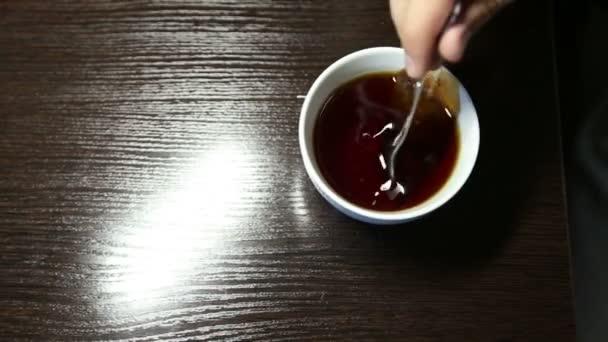 Muž míchací lžička cukru v šálku čaje