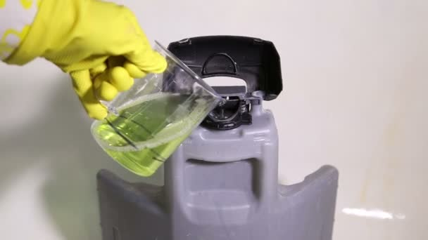 Service cleaner pours detergent into the tank of the vacuum cleaner