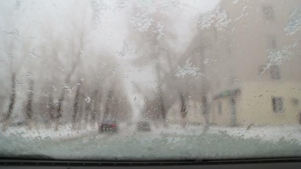 Tání sněhu teče přes čelní sklo auta