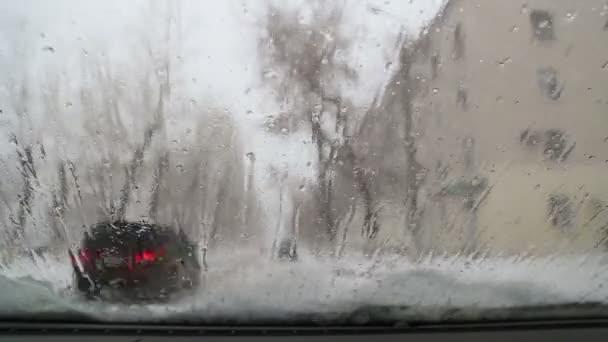 Tání sněhu teče přes čelní sklo automobilu, time-lapse