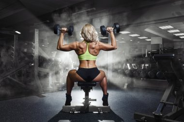 Sexy young girl resting after dumbbells exercises. Fitness woman