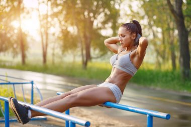 Beautiful fitness woman doing exercise on bars sunny outdoor. Sporty girl doing sit-ups on bars outdoors