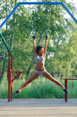 Beautiful fitness woman fitness workout on gymnastic rings sunny outdoor. Sporty girl doing sit ups on gymnastic rings outdoor