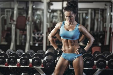 Sexy young girl resting after dumbbells exercises. Fitness woman in blue sport wear with perfect fitness body resting in gym