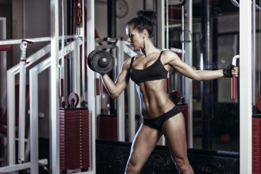 Fitness woman doing exercises with dumbbell in the gym. Brunette fitness girl in black sport wear with perfect body performing biceps exercises